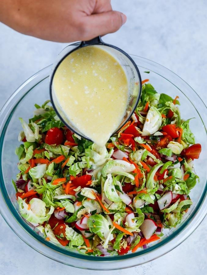 pouring salad dressing on veggies