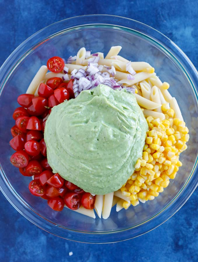 Glass bowl with penne pasta, corn, grape tomatoes, dicd purple onion, and jalapeños with creamy avocado dressing on top on a blue counter.