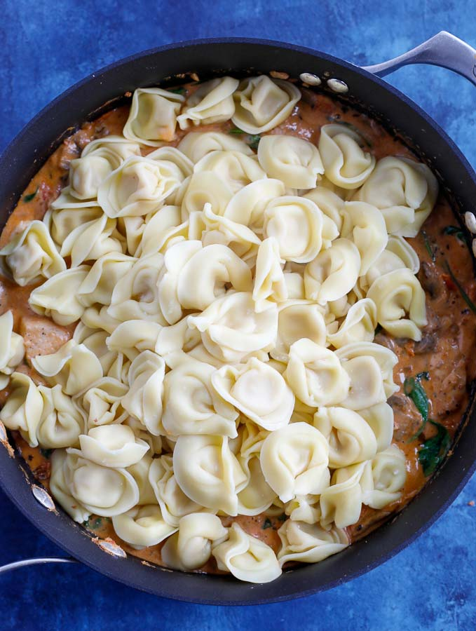 4 cheese tortellini added to the skillet with creamy tortellini sauce, chicken, and spinach.