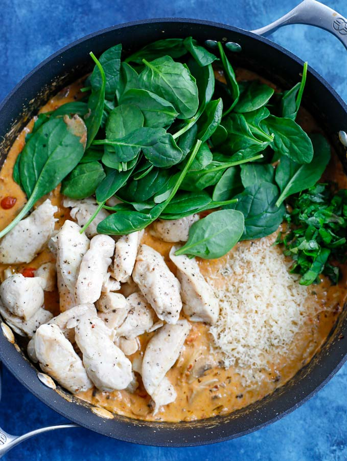 A skillet with creamy pasta sauce, the cooked chicken, and raw spinach on a blue counter.