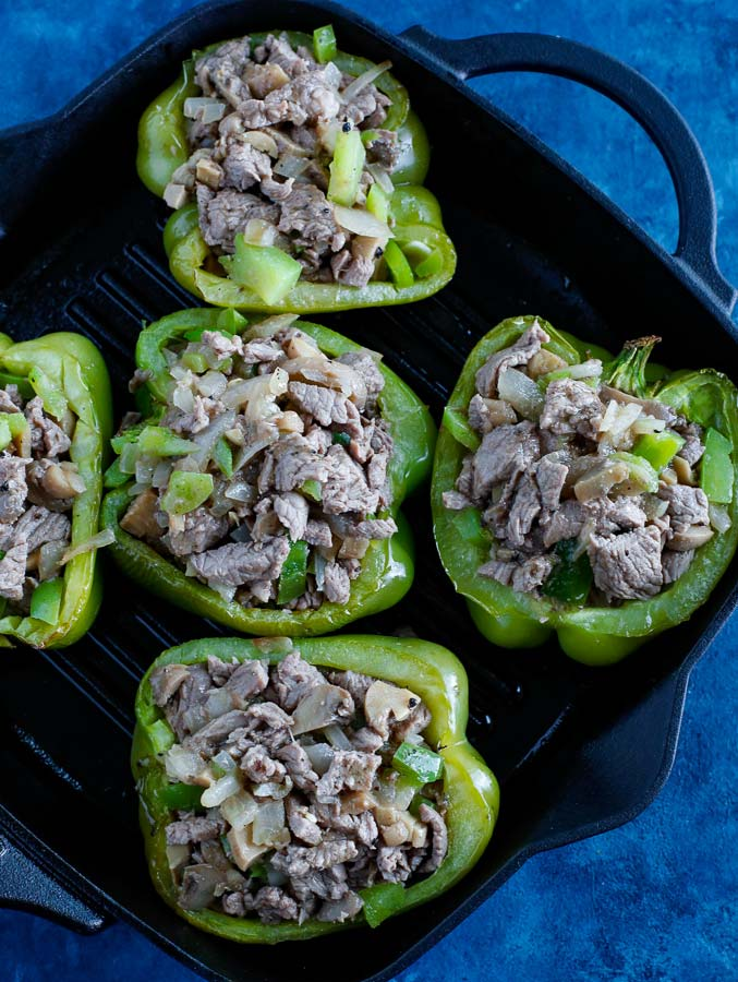 Stuffed bell peppers cooking on a skillet on a blue counter.