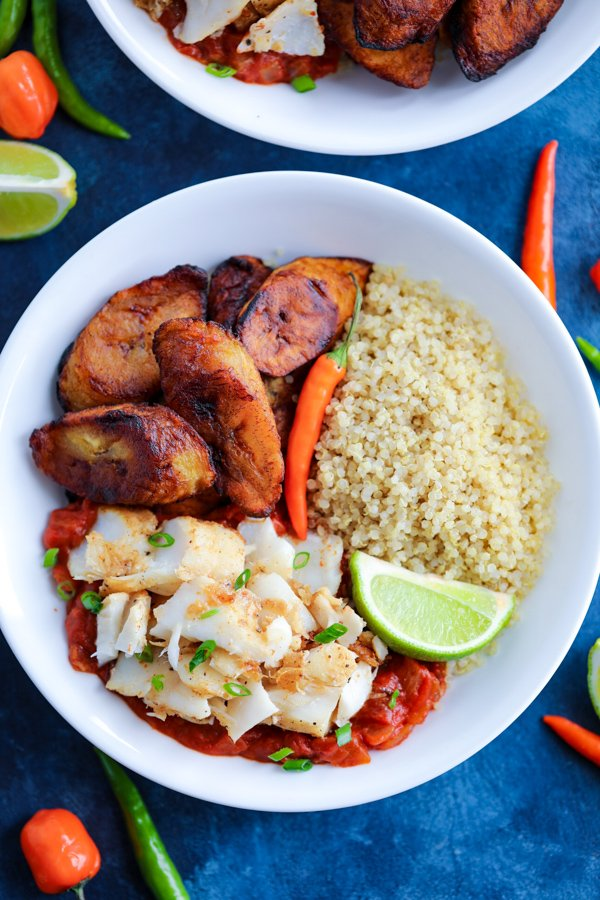 A white bowl with Caribbean Jerk Fish, quinoa, tomato sauce, and fried plantains topped with chilies on a blue counter.