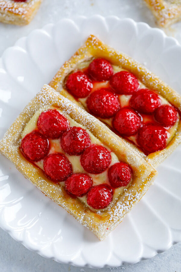 Two raspberry puff pastry tarts on a white plate.