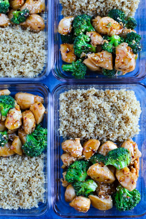 Meal prep containers with Spicy Teriyaki Chicken with Broccoli and brown rice on a blue counter.