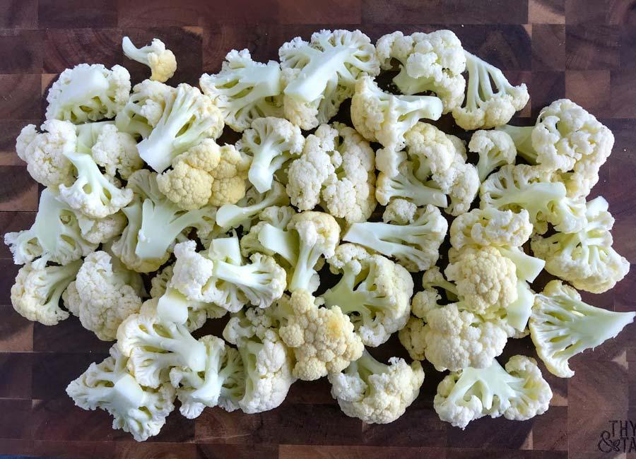 Fresh cauliflower florets cut on a wooden cutting board.