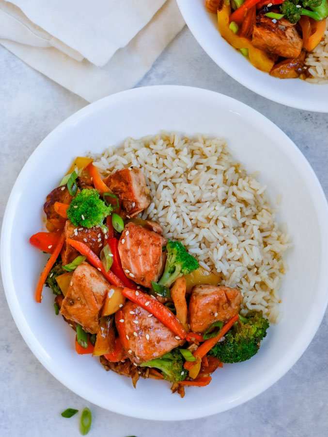 Teriyaki Salmon Stir Fry in a white bowl with rice on a white counter.