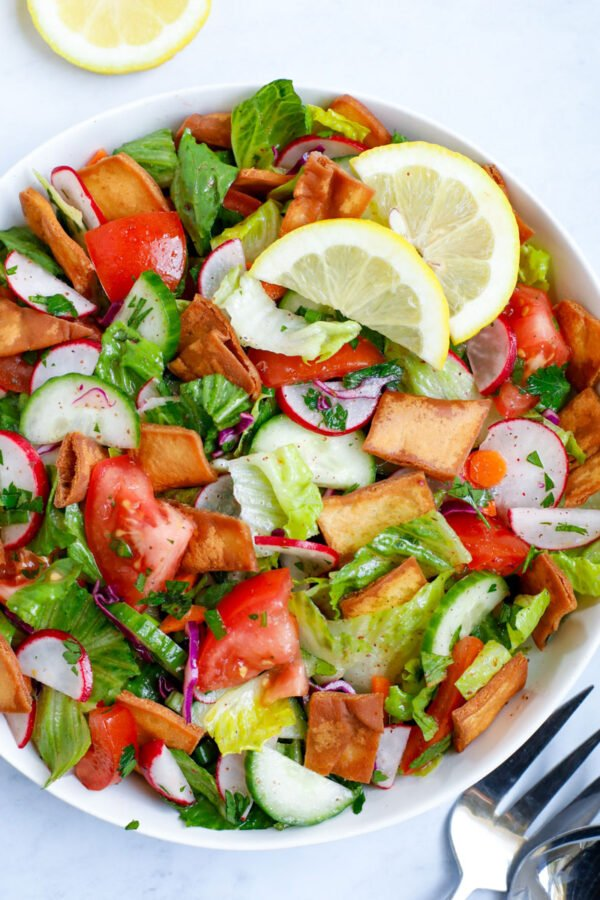 Lebanese Fattoush salad served in a white bowl with lemon slices