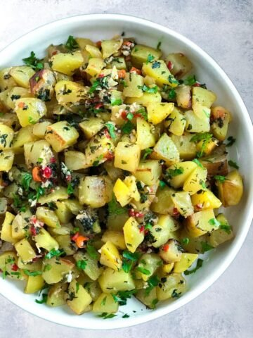 potato cubes friend with cilantro, galic and peppers. served on a plate.