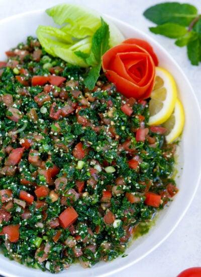 Lebanese tabbouleh garnished with sliced lemons and vegetables