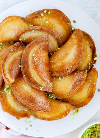 Fried atayef garnished with ground pistashios