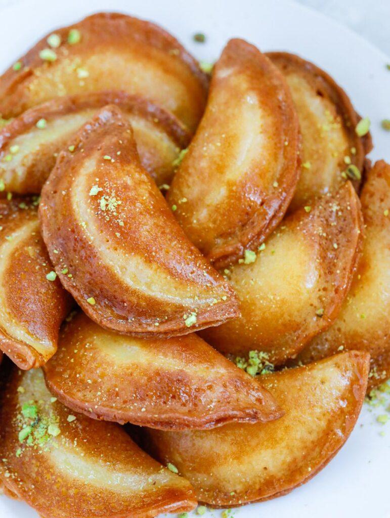 fried atayef garnished with ground pistachios