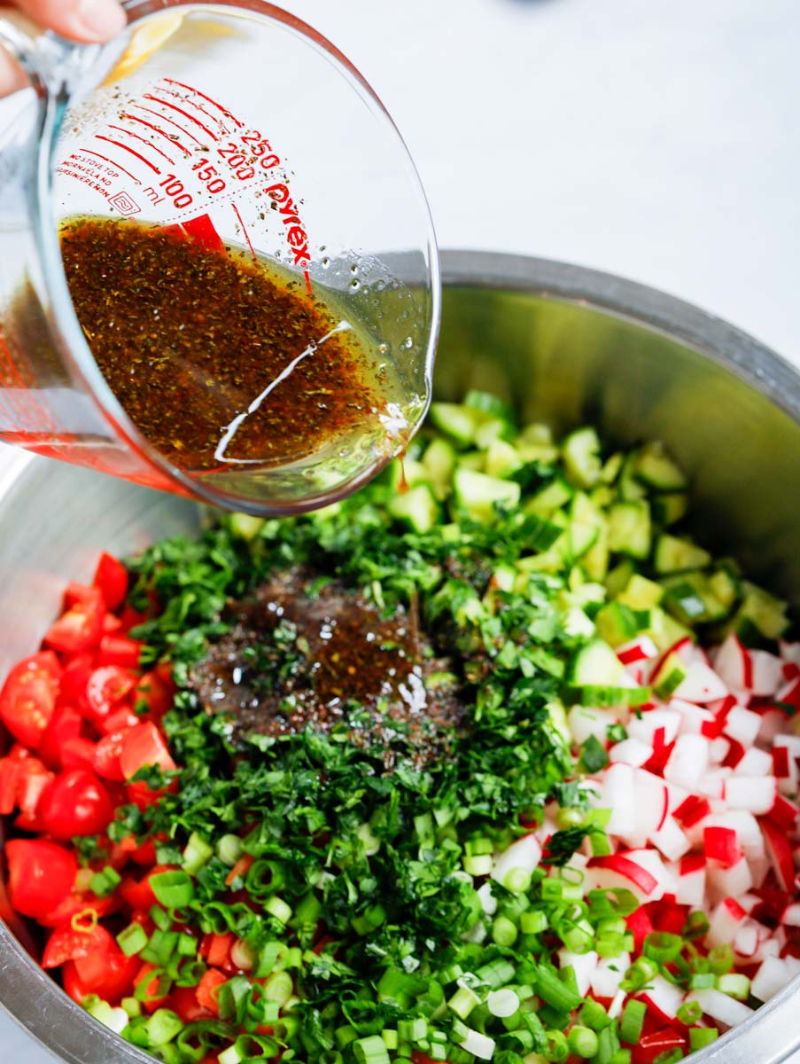 Dressing being poured over the cabbage fattoush salad