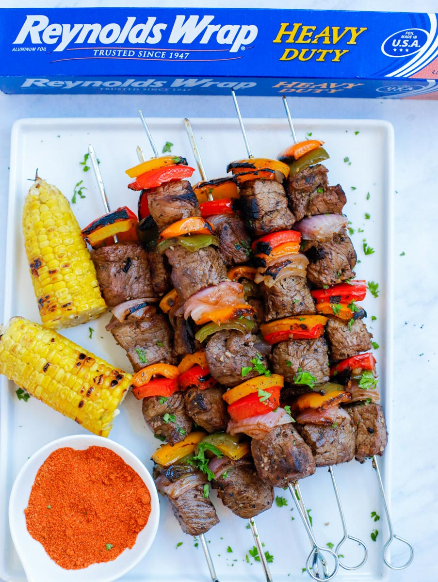 Grilled beef kebobs on a white plate