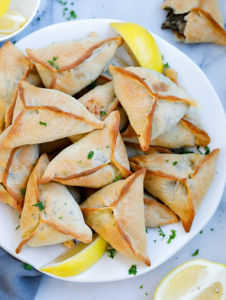 Lebanese Spinach Pie served on a plate with lemon wedges and garnished with parsley