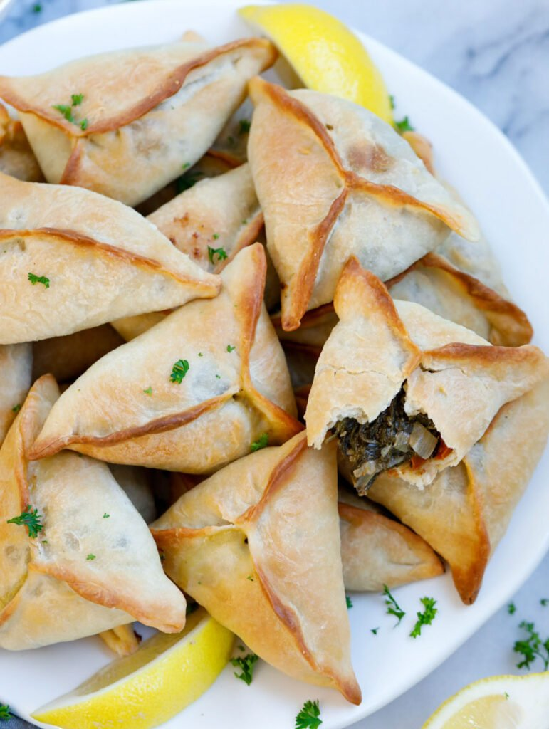 baked lebanese spinach pies served on a plate with lemon wedges