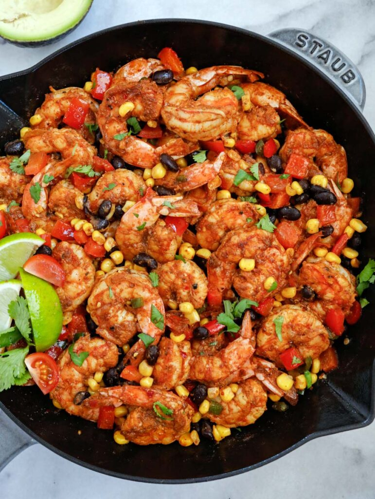 mexican shrimp in a skillet with lemon wedges and cilantro