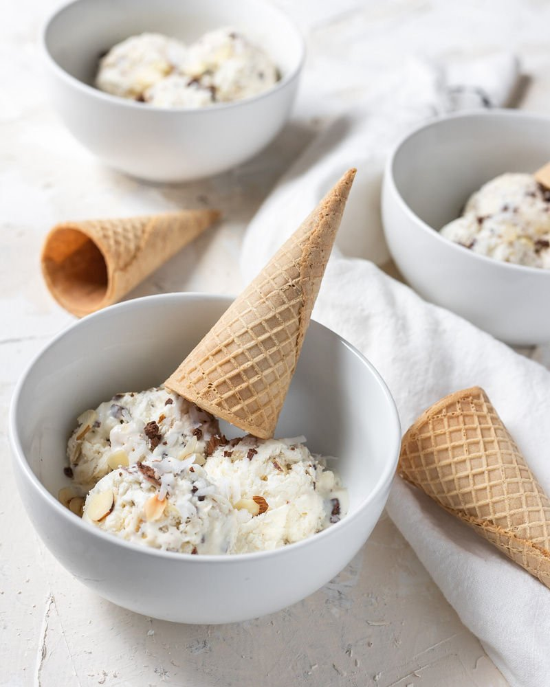 almond joy ice cream in a bowl topped with a cone