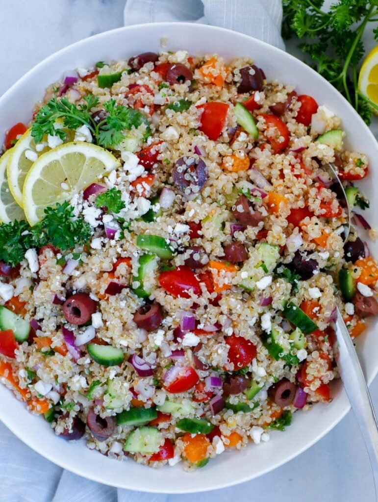 mediterranean quinoa salad served in a dish, dopped with feta cheese and lemon wedges