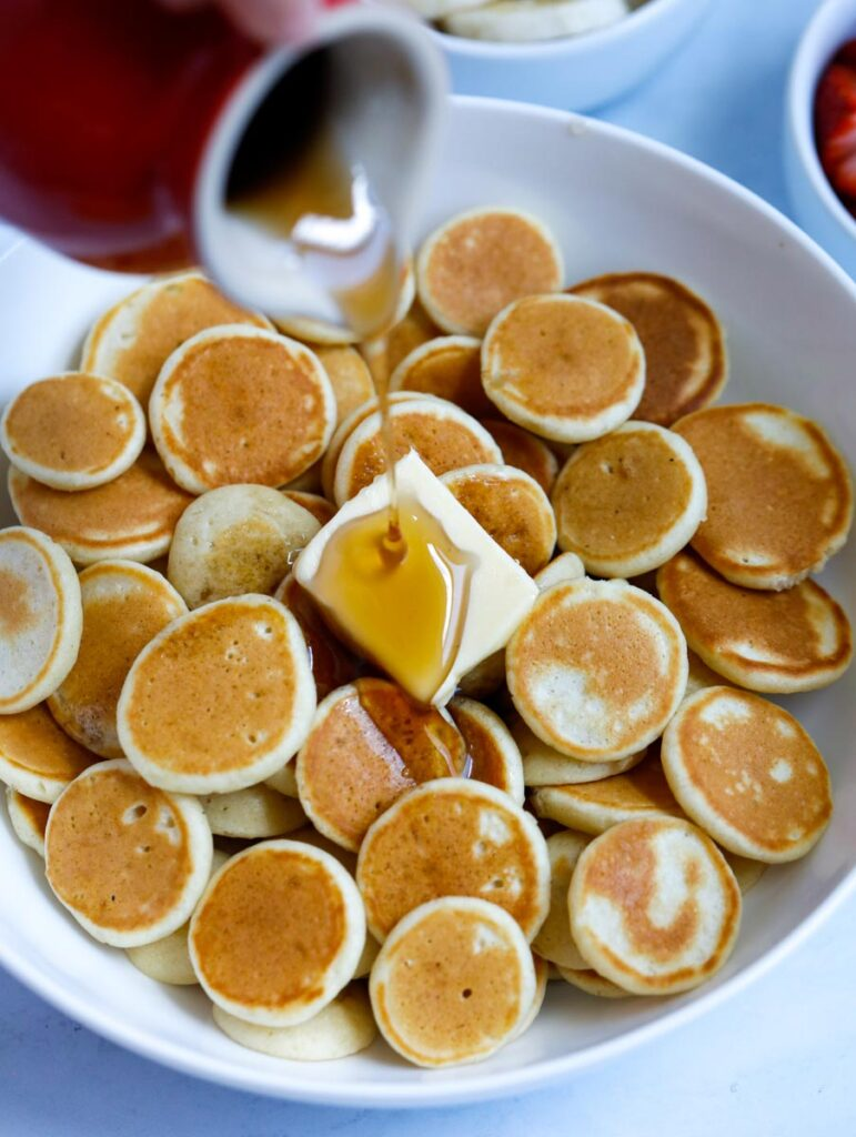 pancake syrup being pour on pancakes