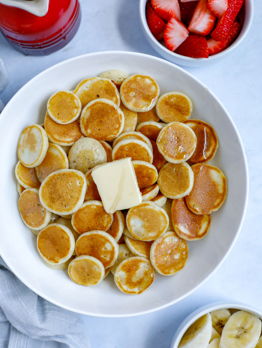 mini pancake cereal served in a bowl with butter and syrup with a side of banana and strawberry fruit