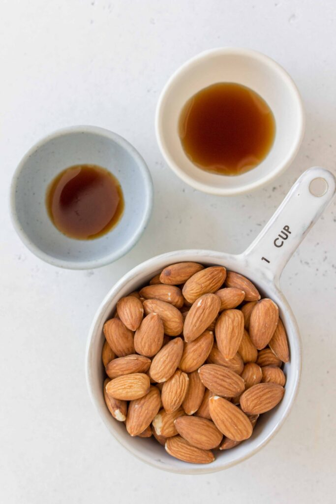 ingredients for almond milk: almonds, maple syrup, and vanilla extract