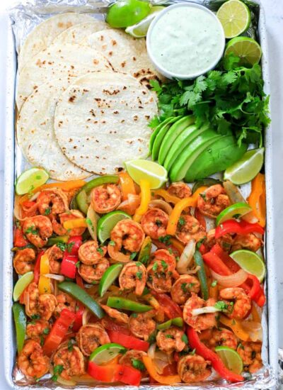 shrimp fajita in a sheet pan with tortilla, avocado and dressing