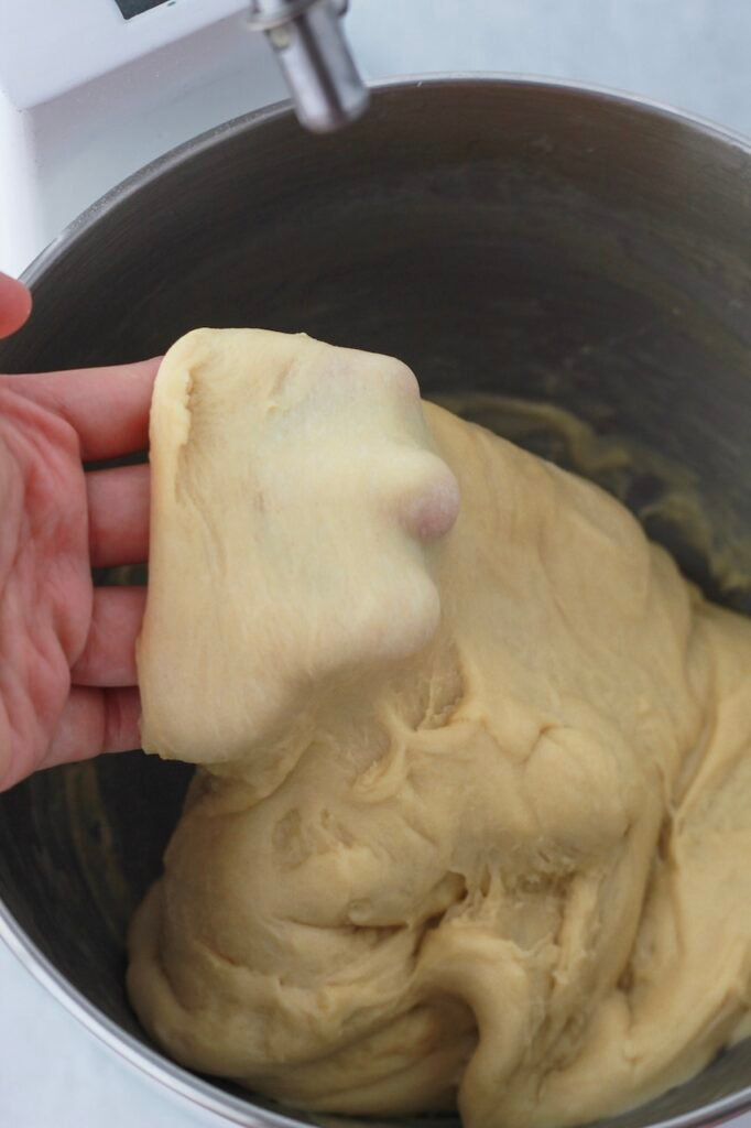 Image of checking if the dinner roll bread dough passes the windowpane test.