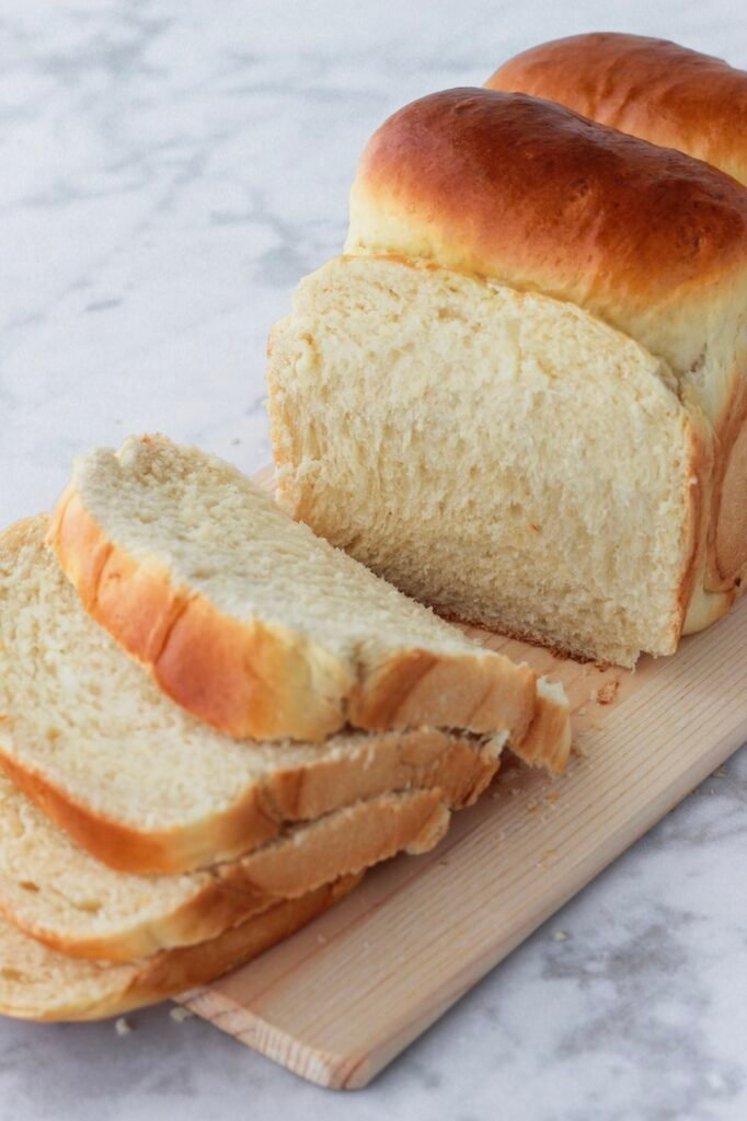 Sandwich loaf being sliced into four slices.