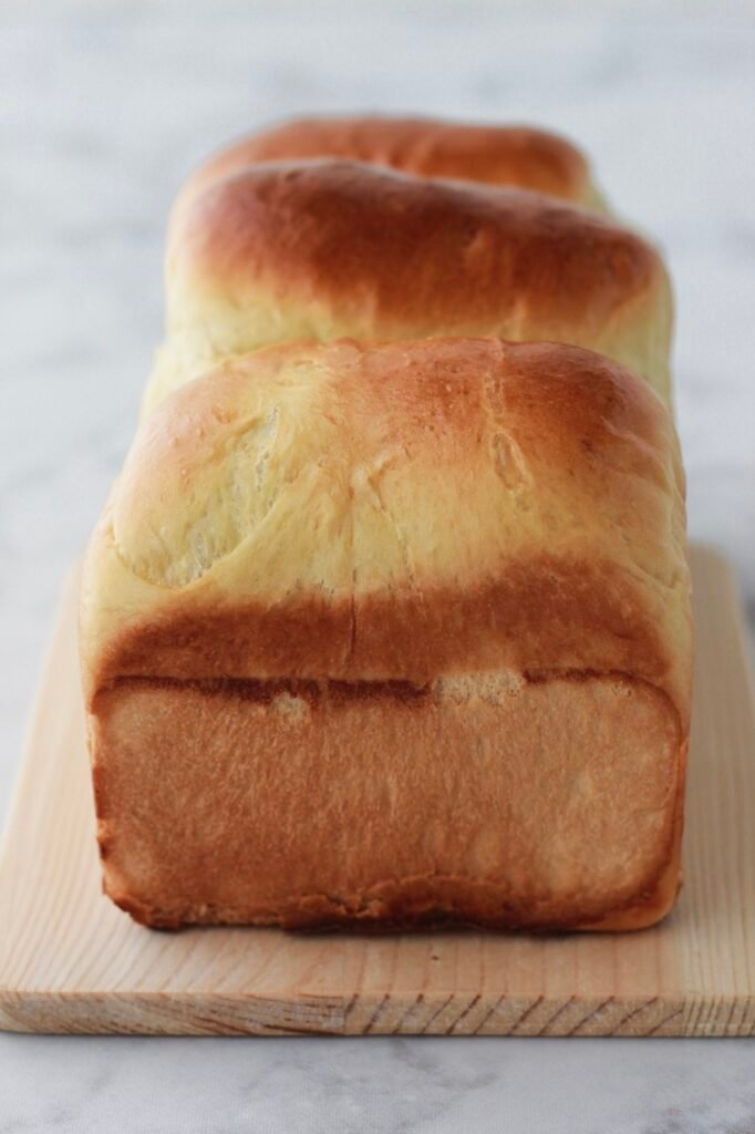 Image of an uncut loaf of freshly baked homemade sandwich bread.