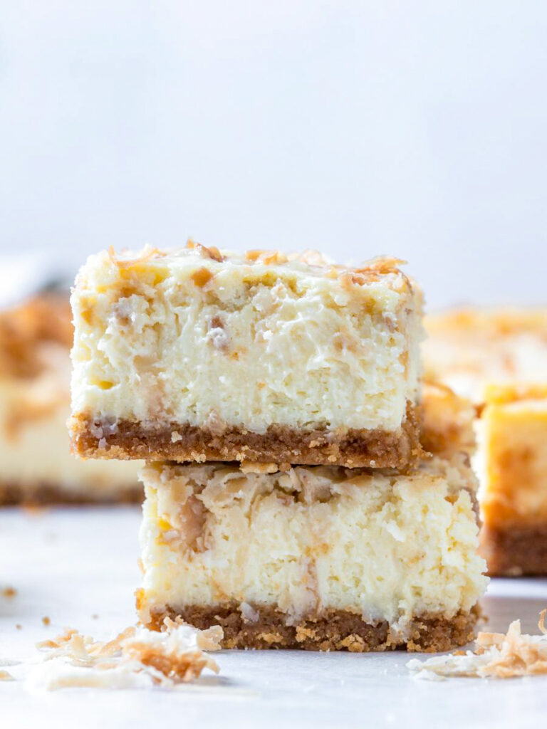 coconut cheesecake bars stacked on top of each other