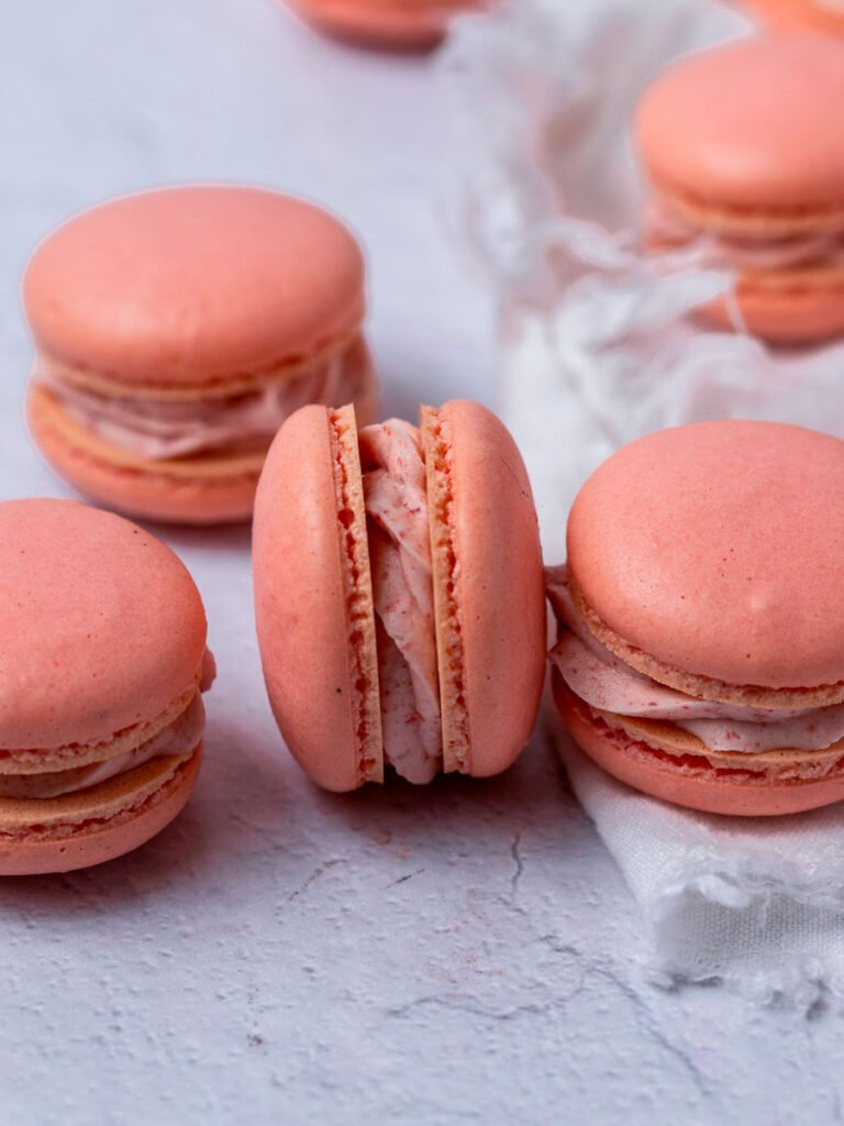 A group of pink French macarons.
