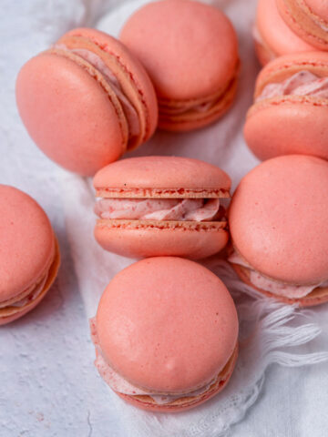 Close up of French macarons with strawberry cream filling.