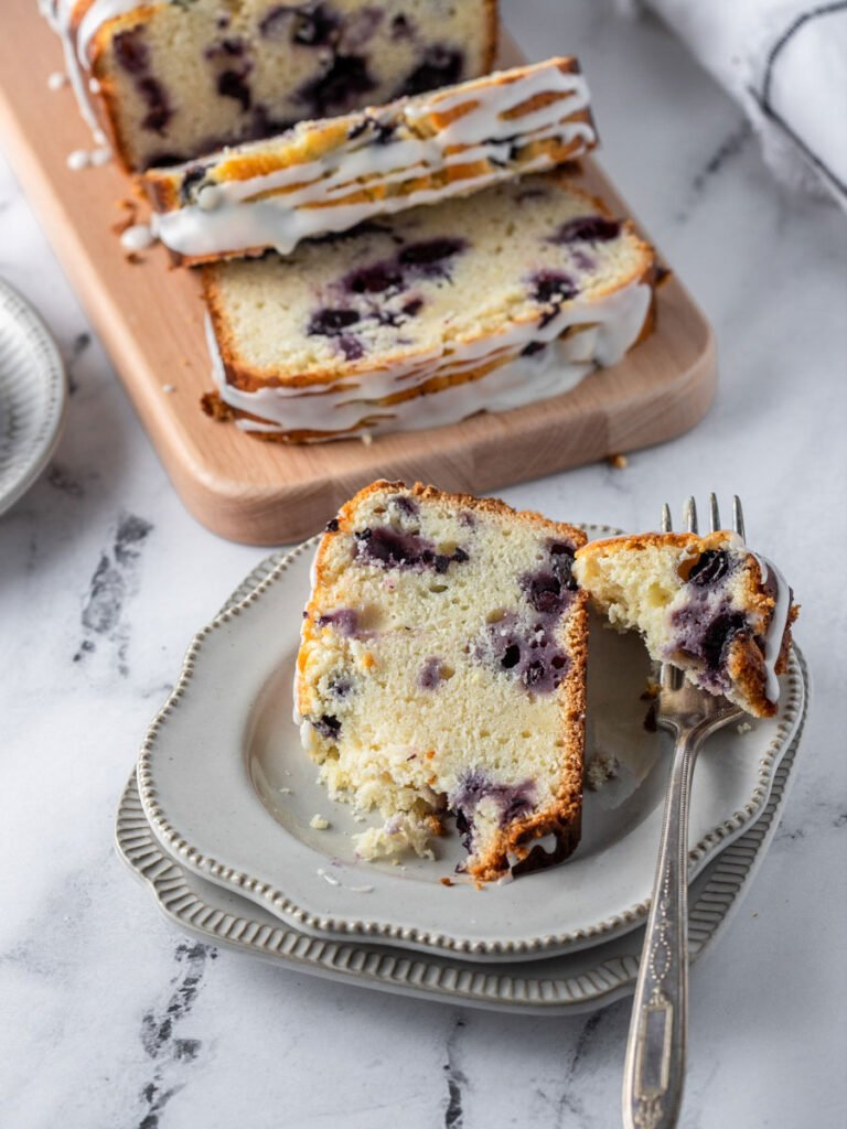 a slice of blueberry lemon bread on a plate with a bite cut off with a fork