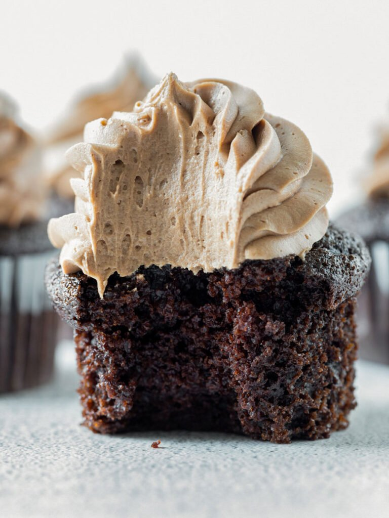 close up shot of chocolate cupcake with a bite taken out of it