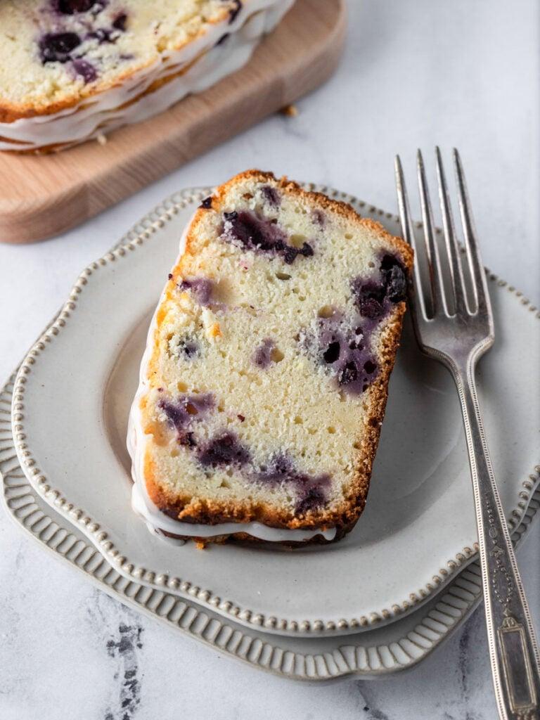 a slice of blueberry lemon bread on a plate