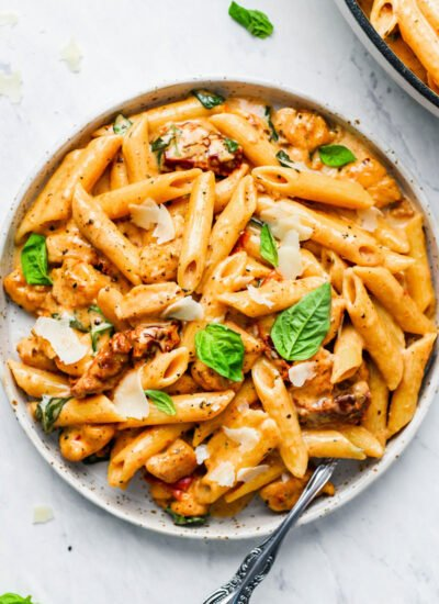 A plate of creamy sun-dried tomato pasta with fresh basil and parmesan shavings on top.
