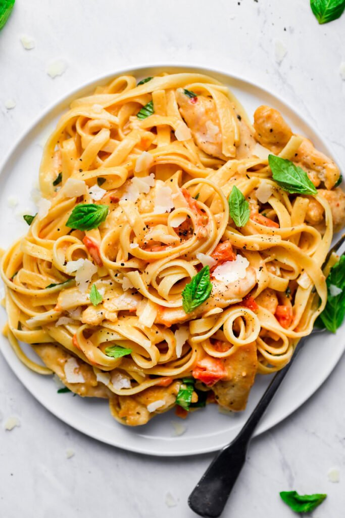 tomato basil pasta served on a white plate with a fork on the side