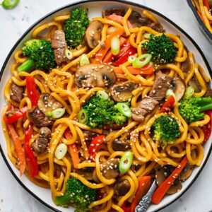 beef lo mein served on a plate and garnished with sesame seeds