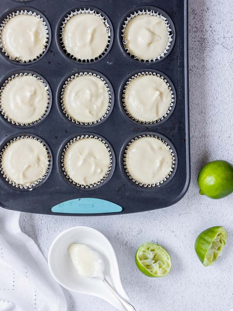 cheesecake filling in a muffin tin pan lined with cupcake holders