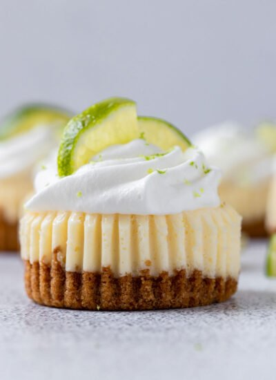 close up shot of mini key lime cupcake with whipped cream and lemon slices on top