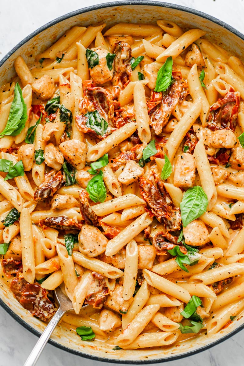 Close up of sun-dried pasta in a pot with fresh basil on top.