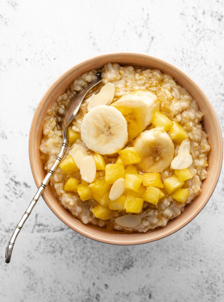 cooked oatmeal in a bowl topped with some pineapple, banana and honey