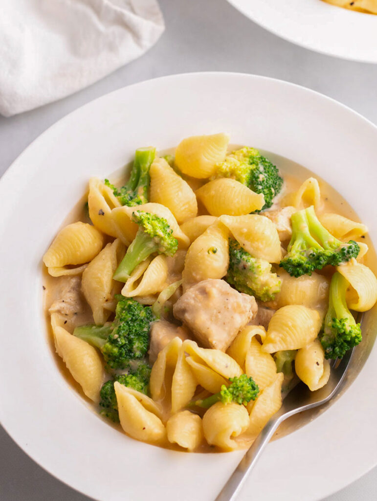 creamy broccoli mac and cheese in a white place with a fork