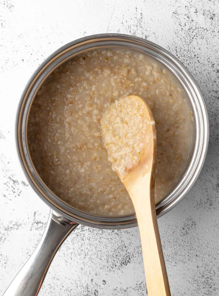 cooked oatmeal in a pot with a wooden spoon scooping some oatmeal