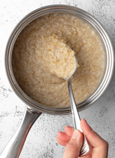 cooked oatmeal in a pot with a spoon scooping some oatmeal
