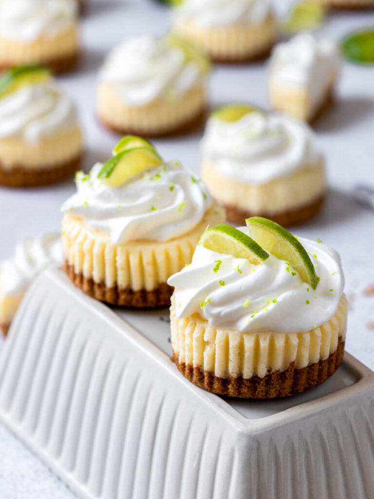mini keylime cheesecake topped with whipped cream and lime slices