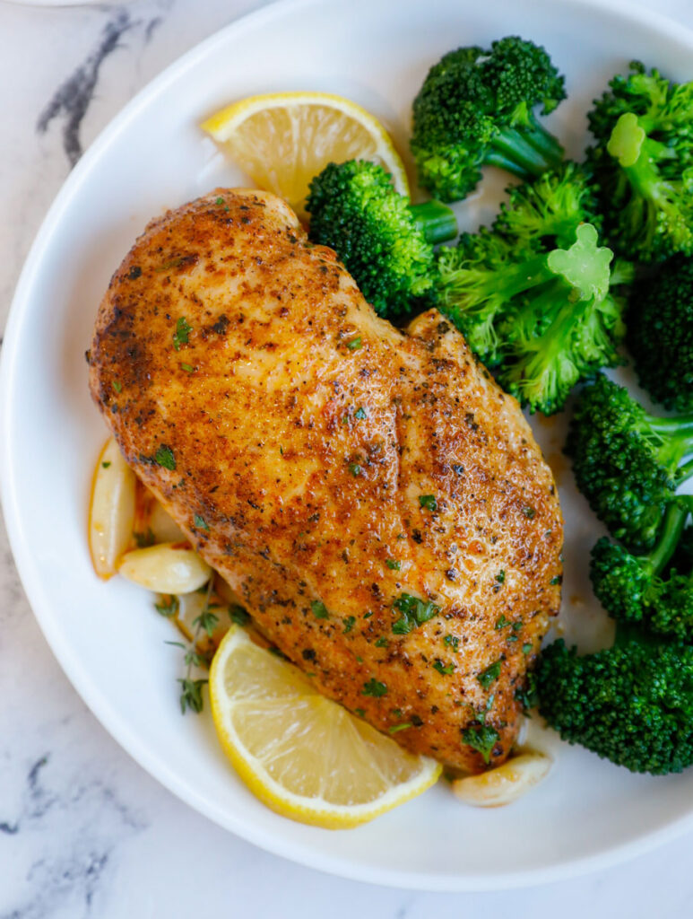 Close up of a chicken breasts beside broccoli florets.