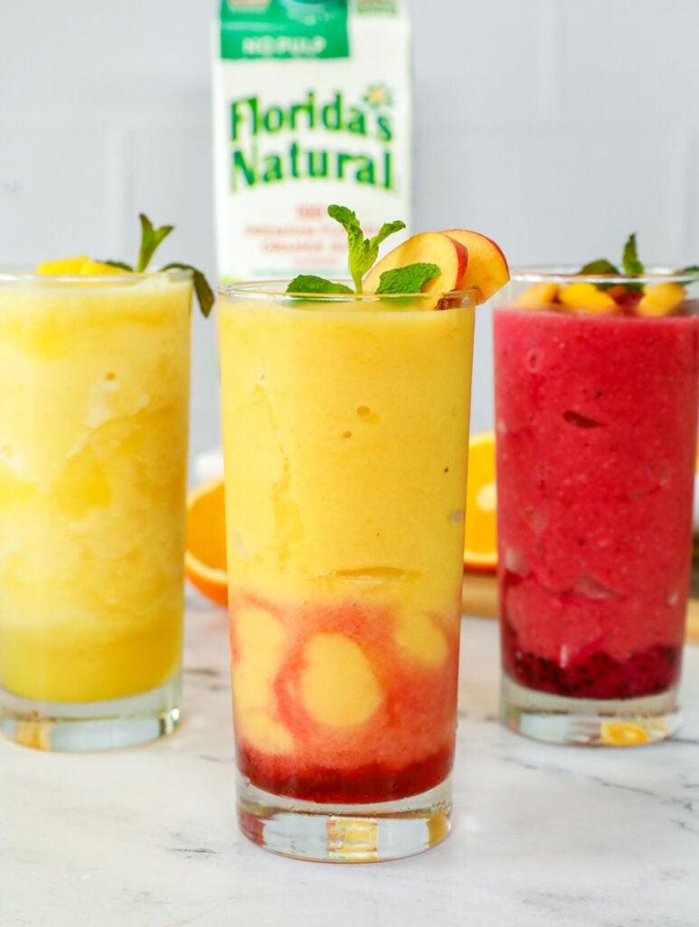 Three glasses of orange juice slushies.