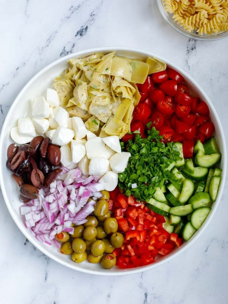 A bowl with all the vegetables for a pasta salad in a bowl.