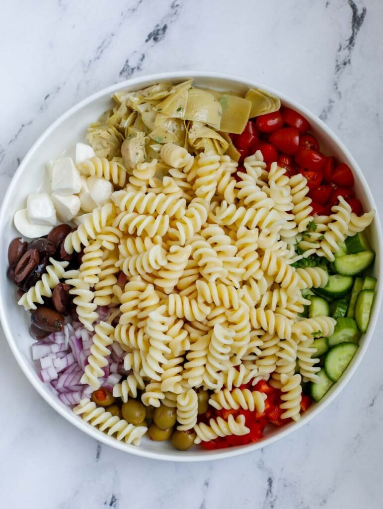 Ingredients for a pasta salad in a bowl.